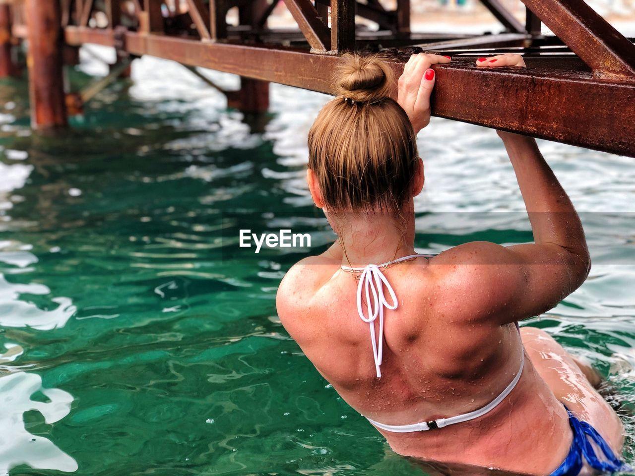 Rear view of woman in bikini hanging on pier in sea
