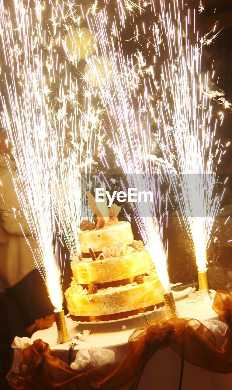 burning, motion, fire, heat - temperature, flame, glowing, fire - natural phenomenon, illuminated, food, night, celebration, blurred motion, close-up, food and drink, nature, long exposure, event, freshness, real people, sweet food, sparks, hand, sparkler, temptation