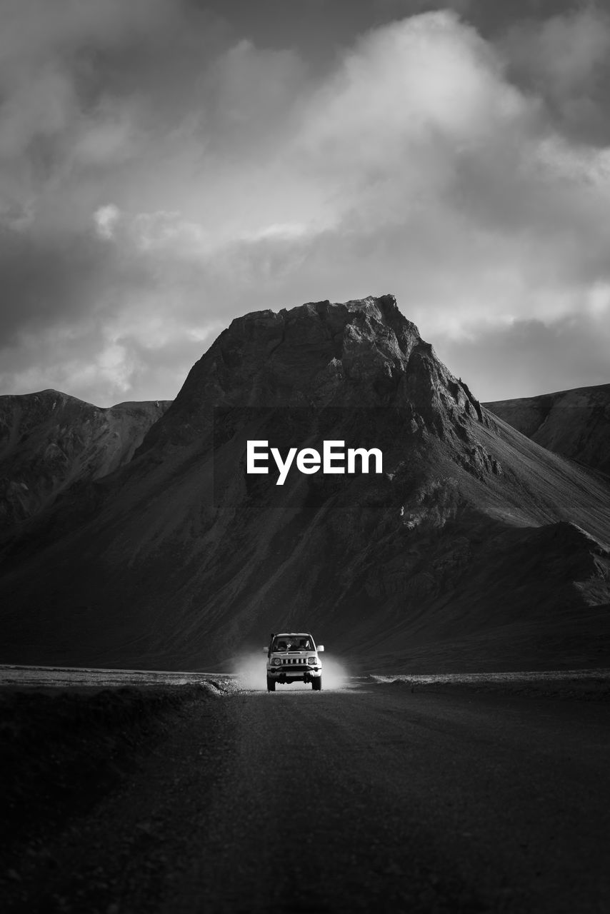 CAR ON ROAD AGAINST MOUNTAIN RANGE