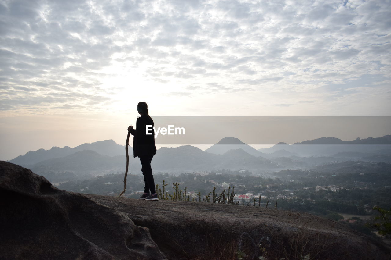 Woman holding stick while standing on landscape against sky during sunset