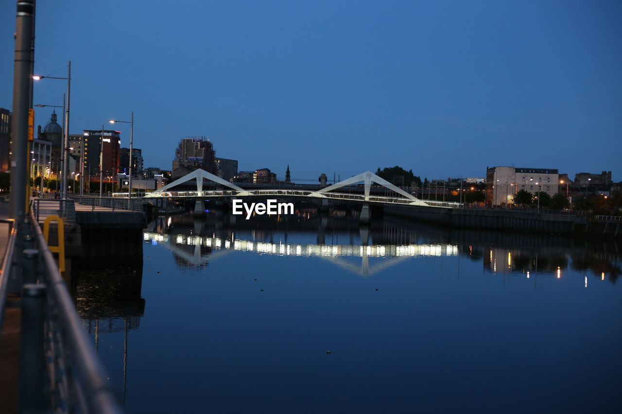 architecture, sky, built structure, reflection, water, building exterior, city, nature, copy space, connection, clear sky, no people, waterfront, river, blue, bridge, building, illuminated, bridge - man made structure, outdoors, skyscraper