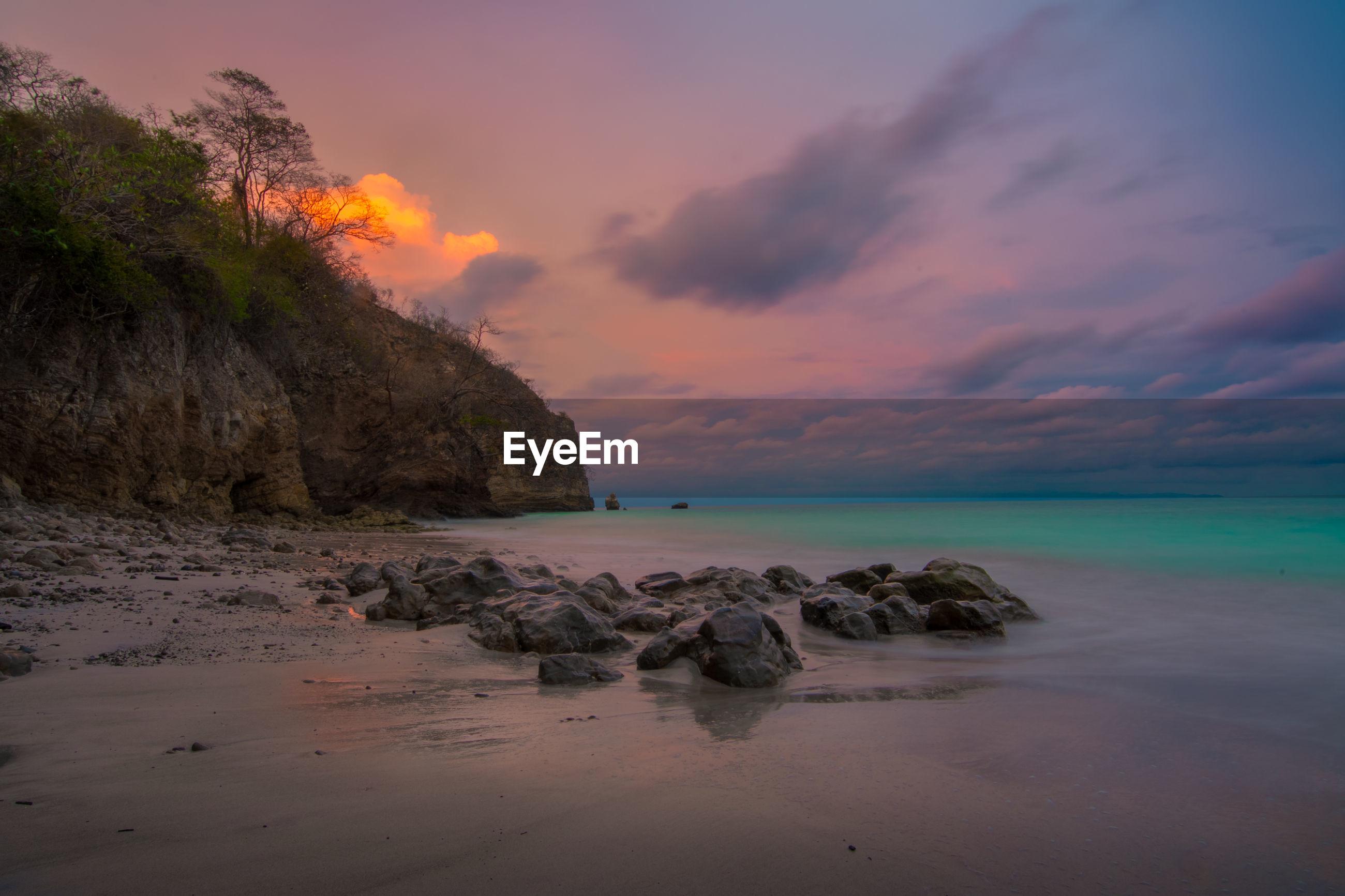 ROCKS ON BEACH AGAINST SKY AT SUNSET