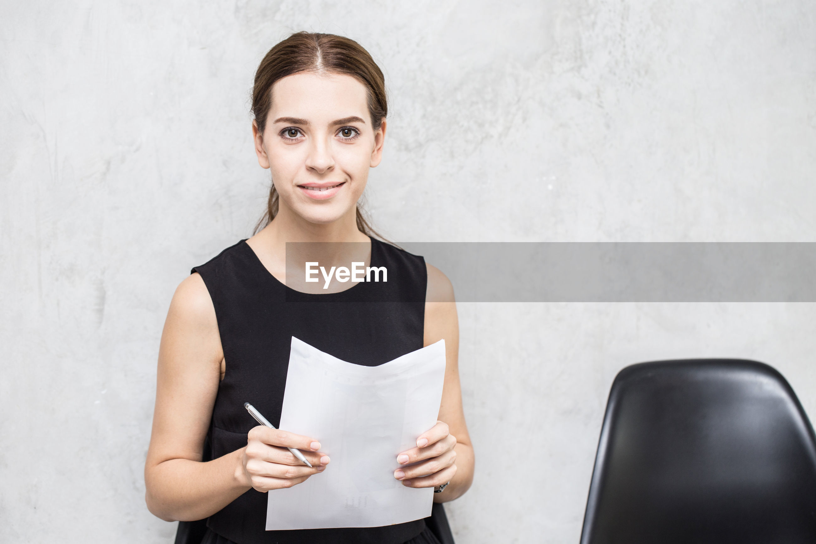 Portrait of businesswoman holding papers against wall