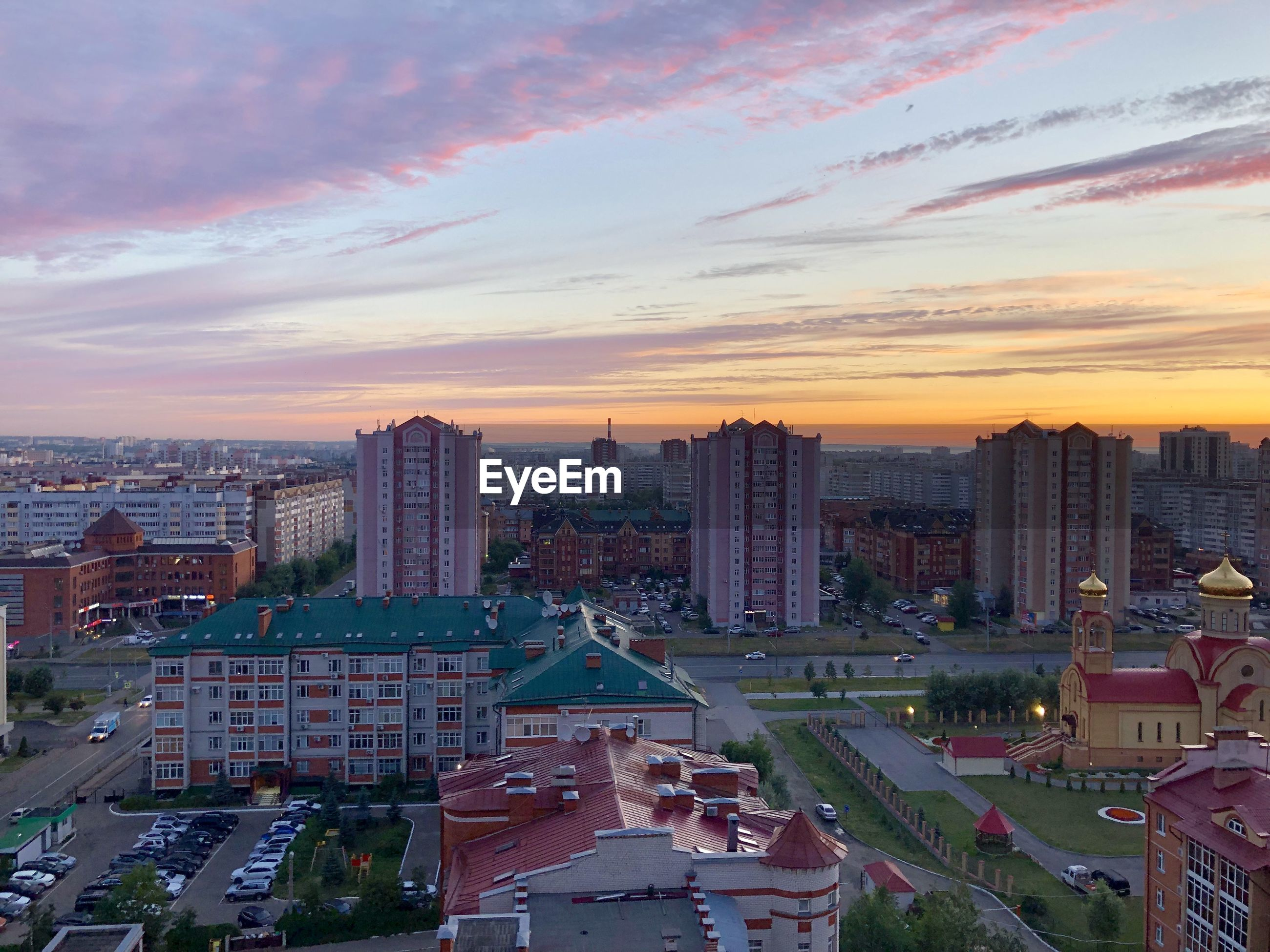 High angle view of modern buildings in city against sky during sunset