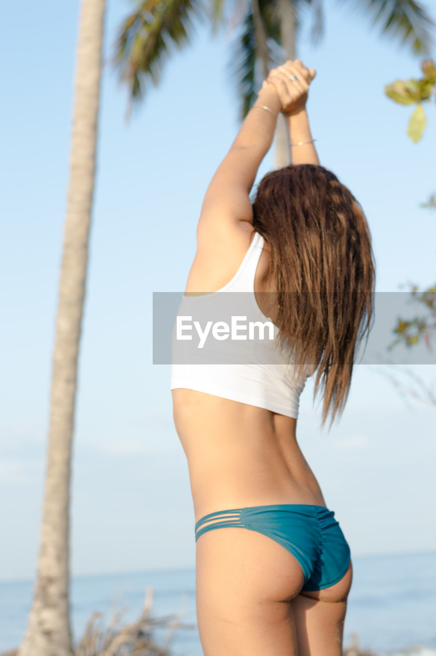 Rear view of sensuous young woman standing at beach