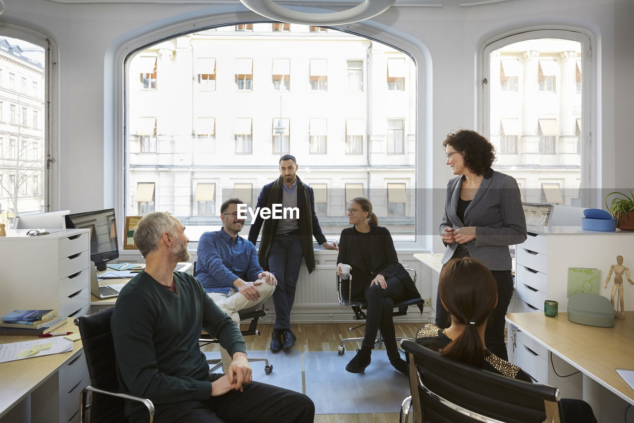 group of people, sitting, women, adult, men, indoors, window, office, group, young adult, businesswoman, medium group of people, males, people, young women, real people, business, table, communication, teamwork, mature men, coworker