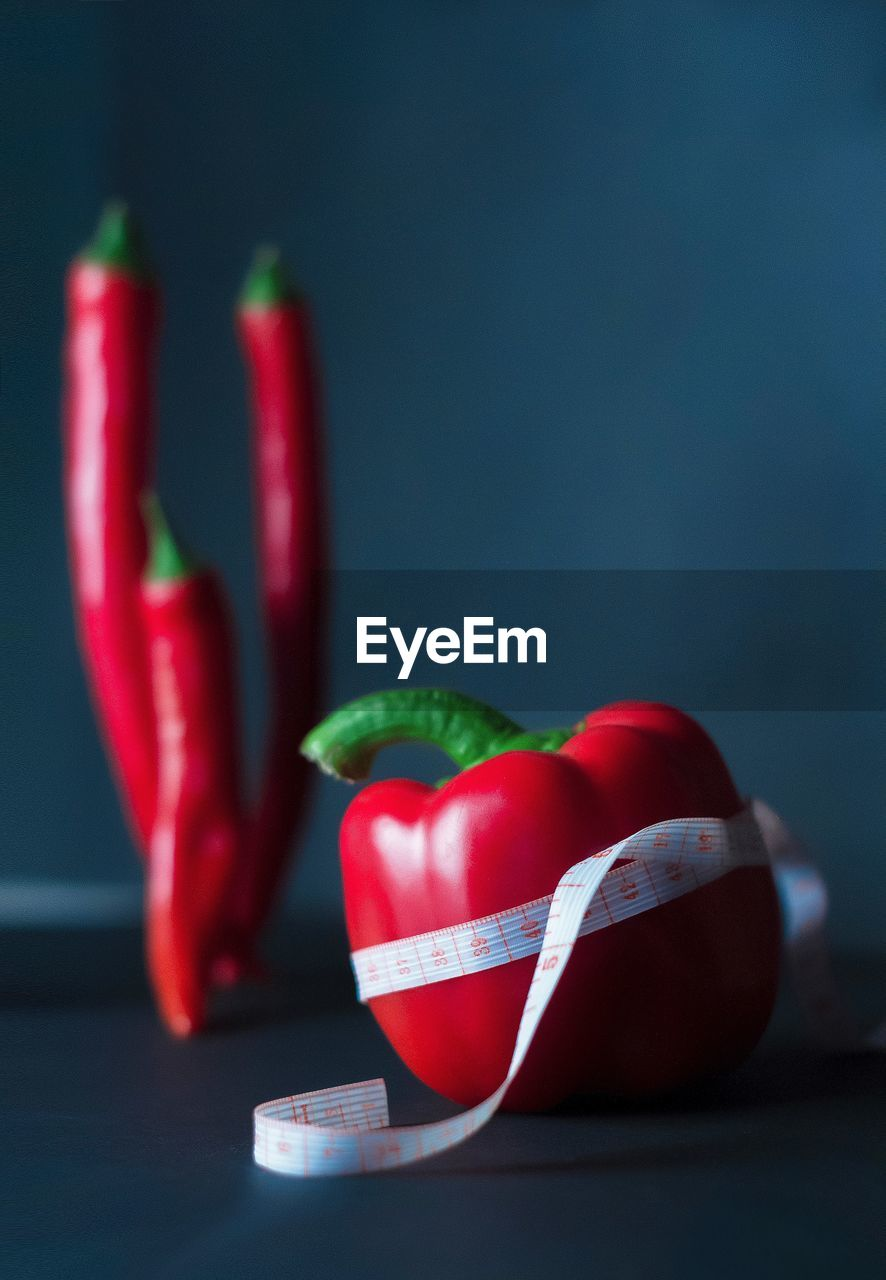 Close-up of red bell pepper with tape measure on table