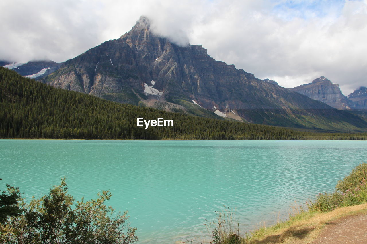 mountain, beauty in nature, water, scenics - nature, lake, plant, sky, nature, landscape, tranquil scene, environment, day, no people, tranquility, cloud - sky, tree, land, mountain range, non-urban scene, outdoors, mountain peak, range, turquoise colored