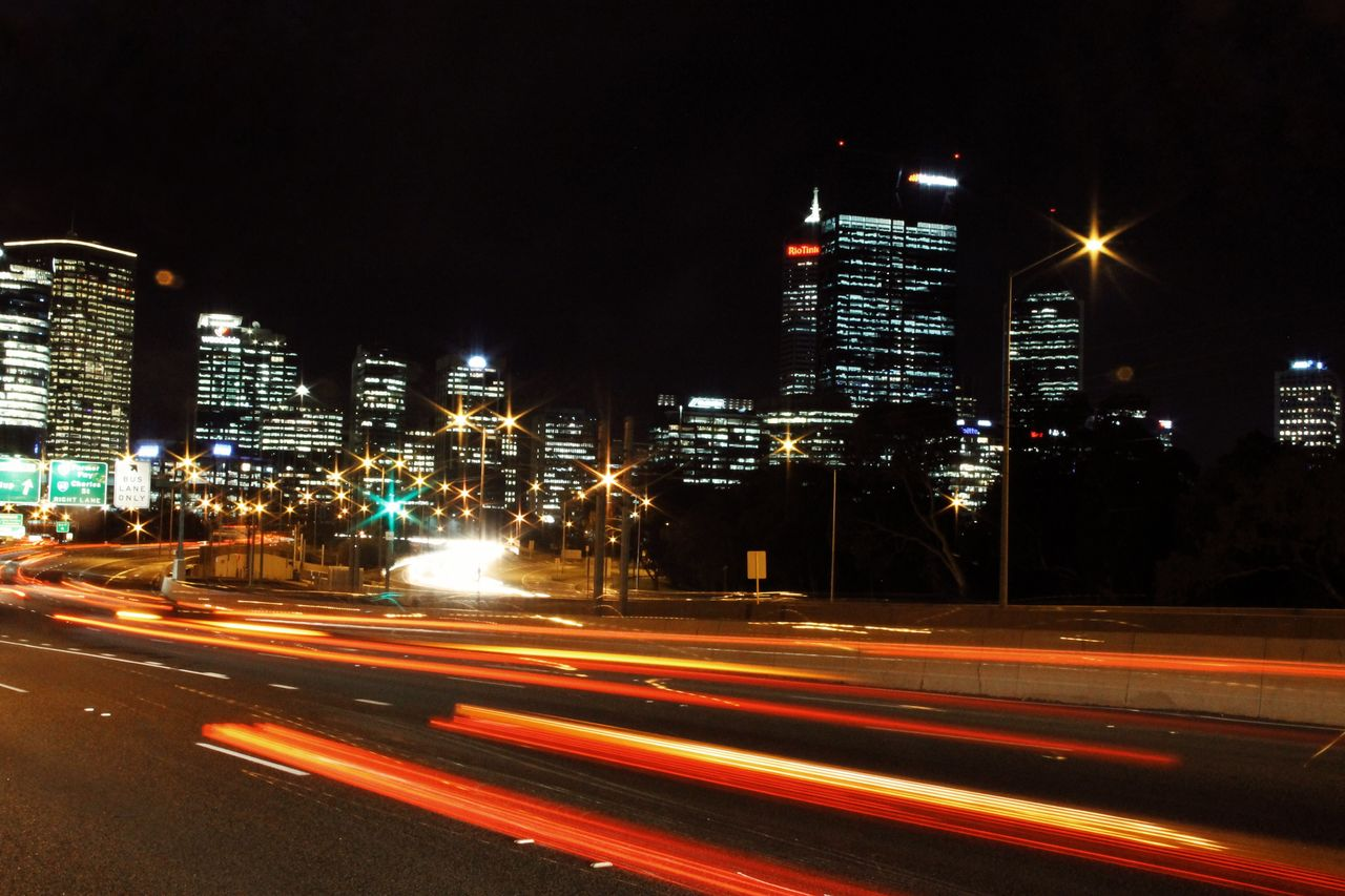 city, illuminated, night, building exterior, long exposure, motion, architecture, built structure, street, light trail, blurred motion, city life, road, speed, building, no people, office building exterior, street light, transportation, cityscape, skyscraper, outdoors, financial district