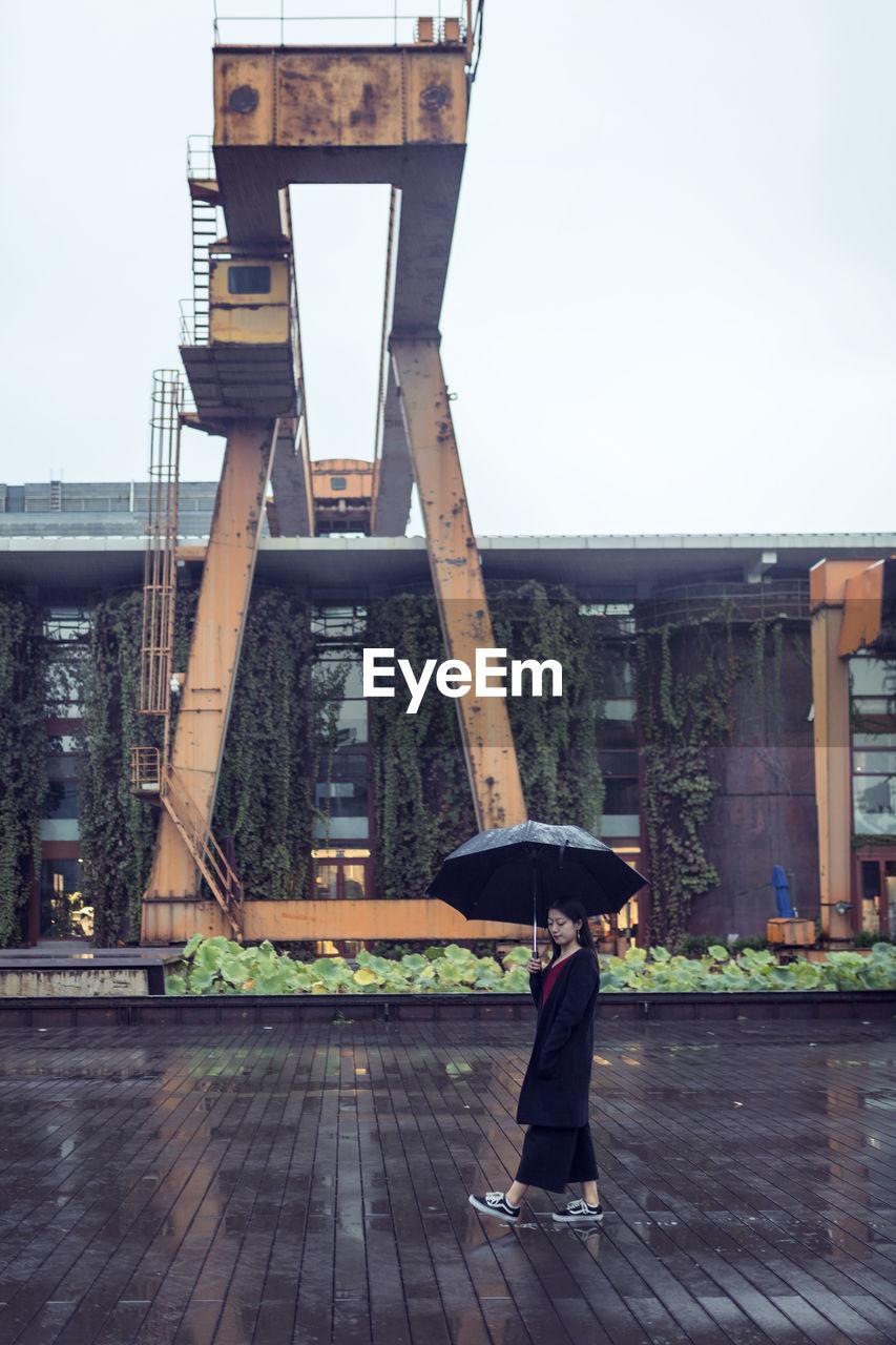 WOMAN WALKING WITH UMBRELLA IN RAIN
