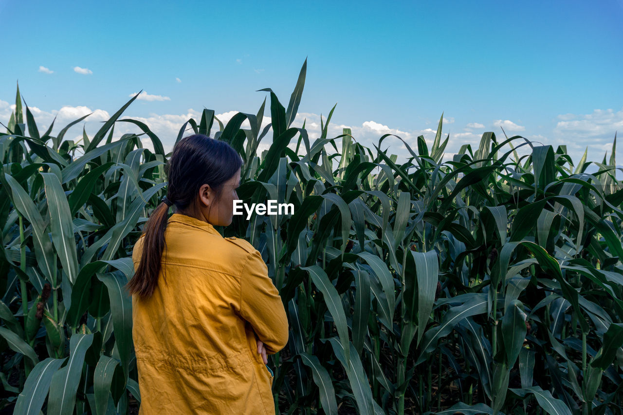 Rear view of woman standing in farm against sky