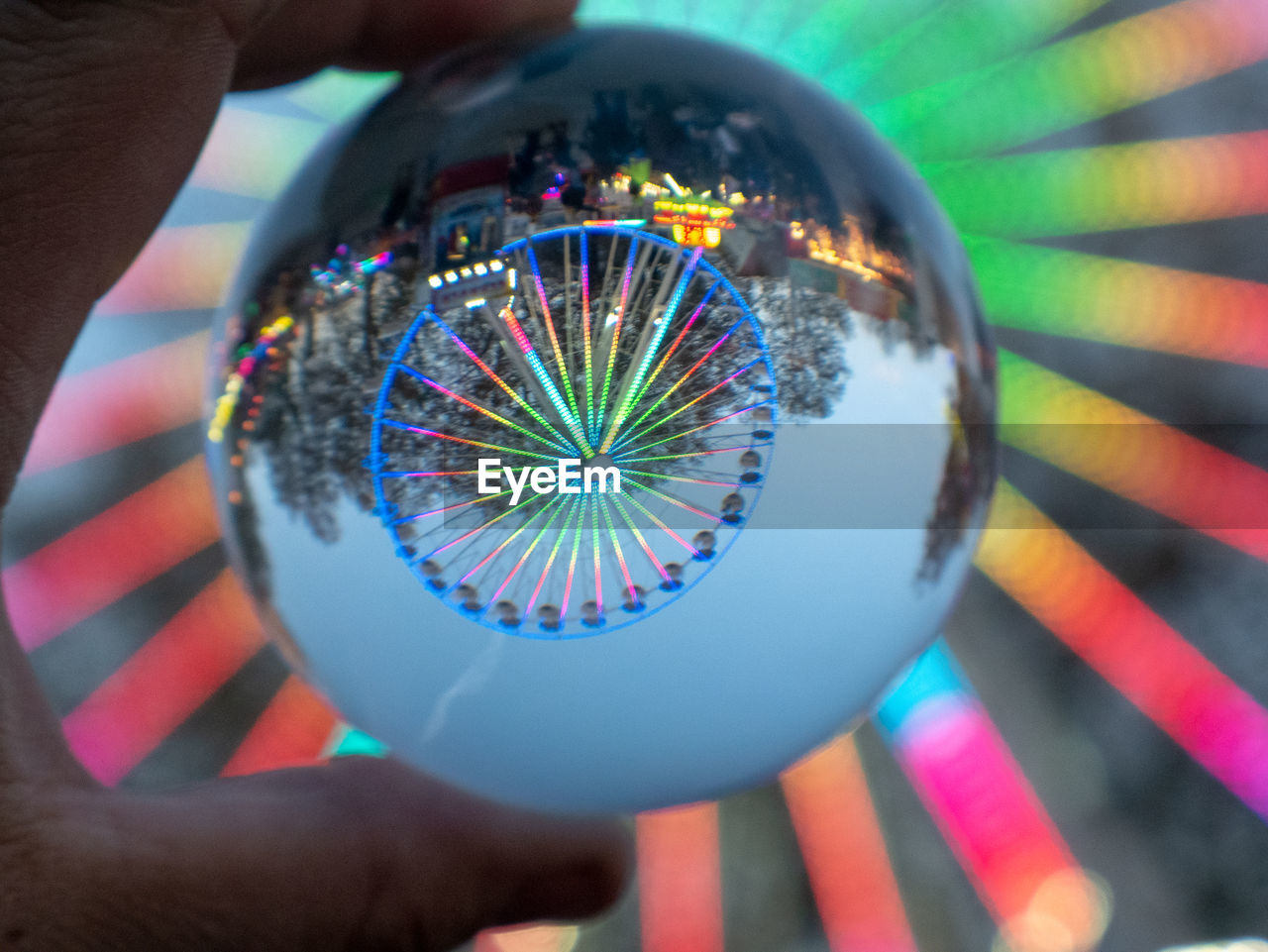 human hand, hand, human body part, holding, real people, one person, unrecognizable person, sphere, leisure activity, lifestyles, finger, close-up, body part, human finger, multi colored, geometric shape, focus on foreground, personal perspective, circle, outdoors