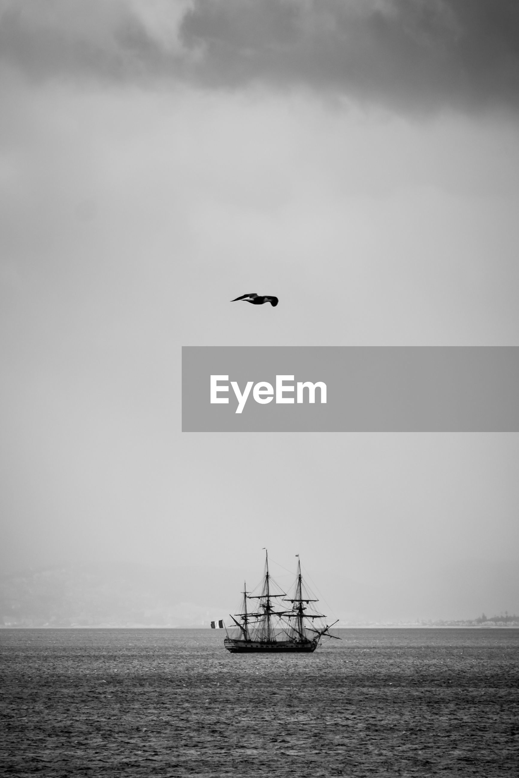 NAUTICAL VESSEL FLYING OVER SEA AGAINST SKY