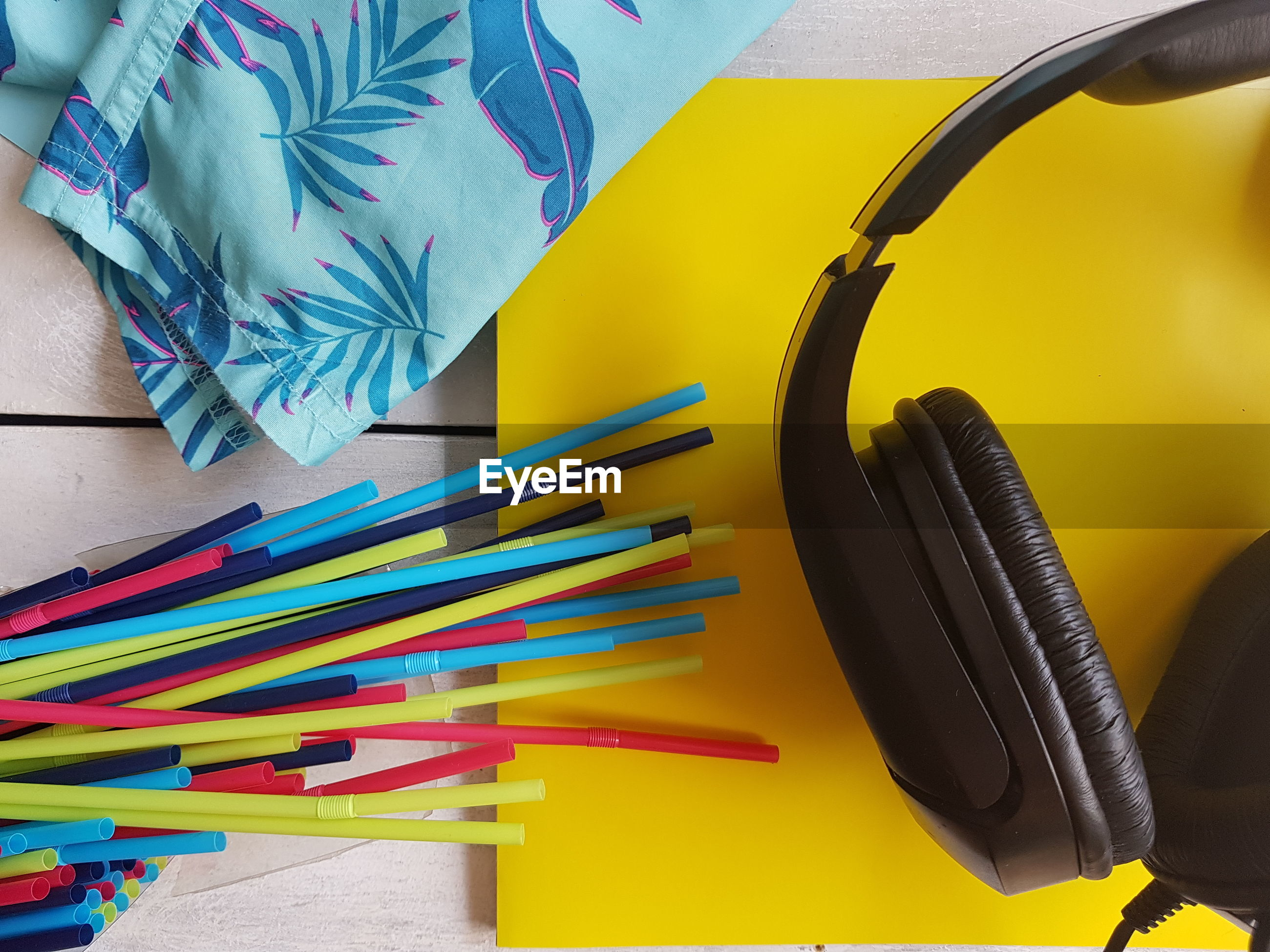 Close-up of drinking straws with headphones on table