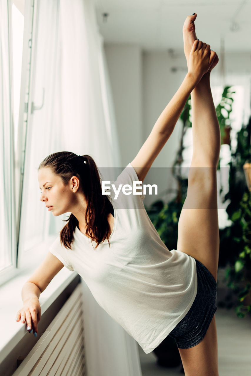 Full length of young woman stretching legs by window at home