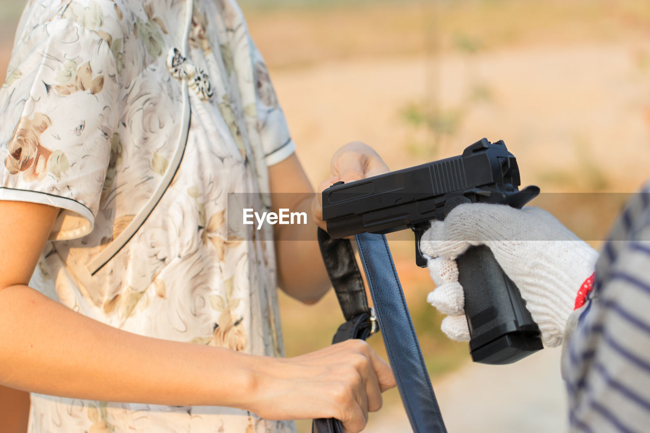 midsection, holding, real people, gun, focus on foreground, weapon, men, people, two people, day, adult, lifestyles, outdoors, women, hand, clothing, leisure activity, human hand, activity, nature, aggression, care