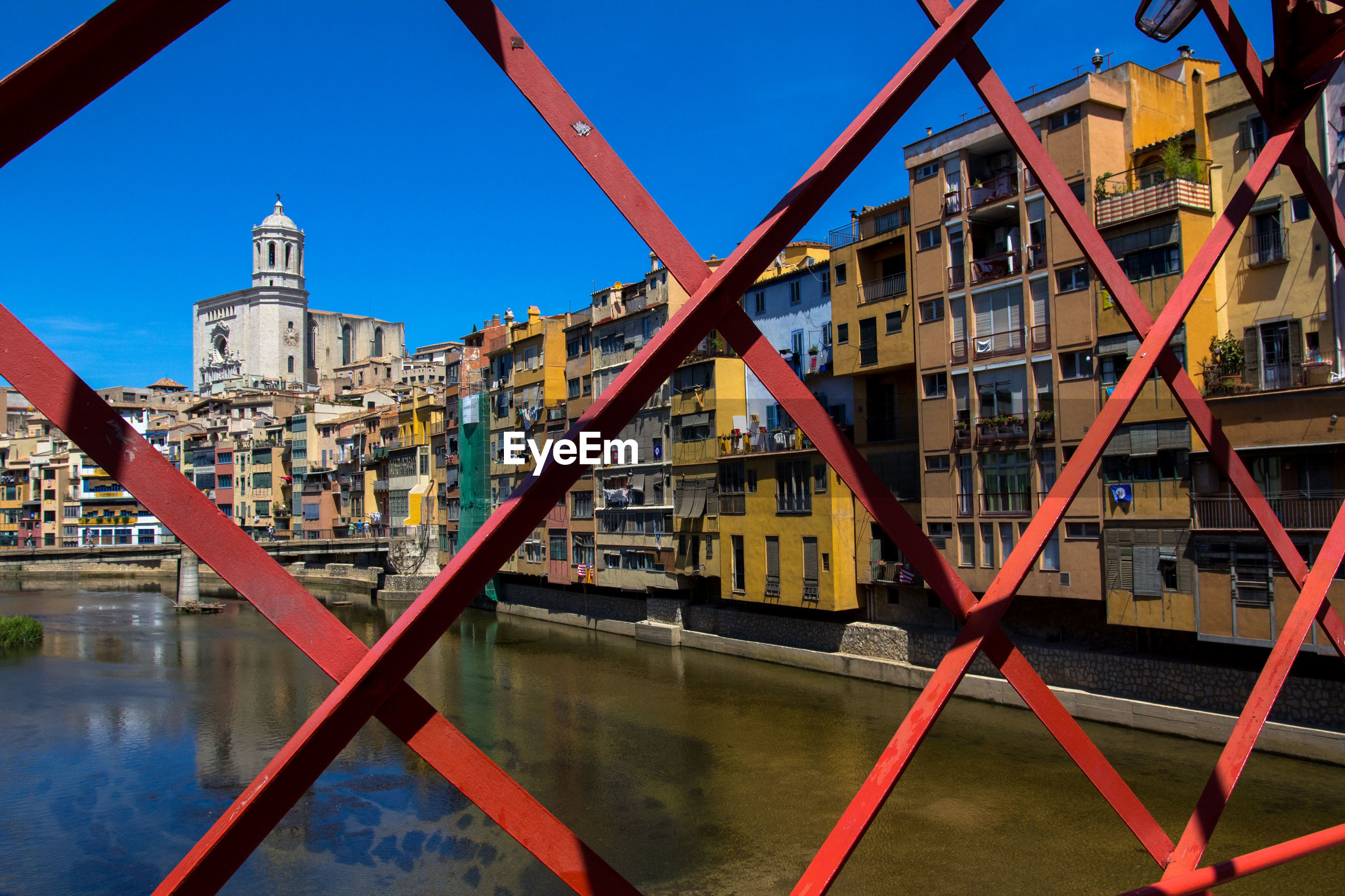 Buildings by river against clear blue sky seen through fence
