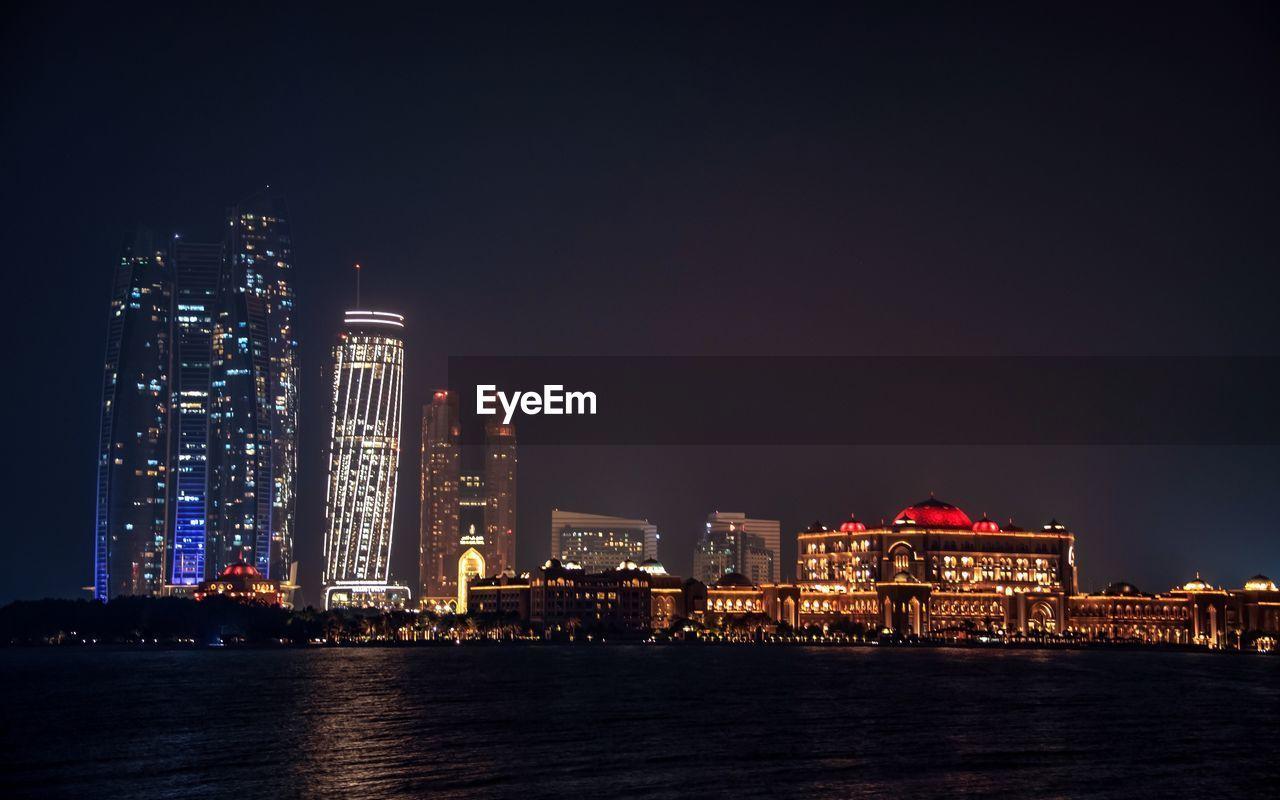 ILLUMINATED CITYSCAPE BY SEA AGAINST SKY AT NIGHT