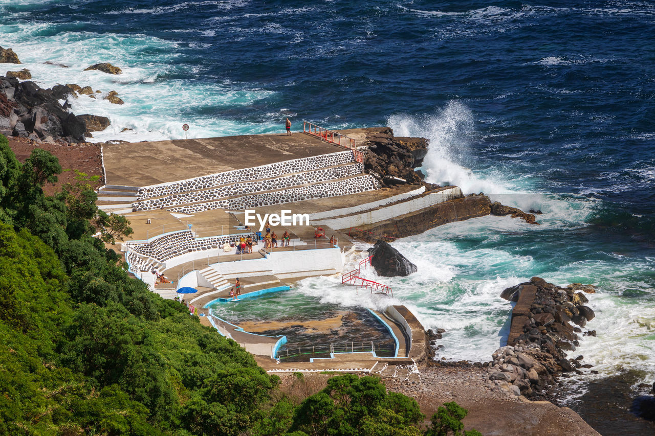 People by a seawater swimming pool foz da ribeira do guilherme on sao miguel island, azores