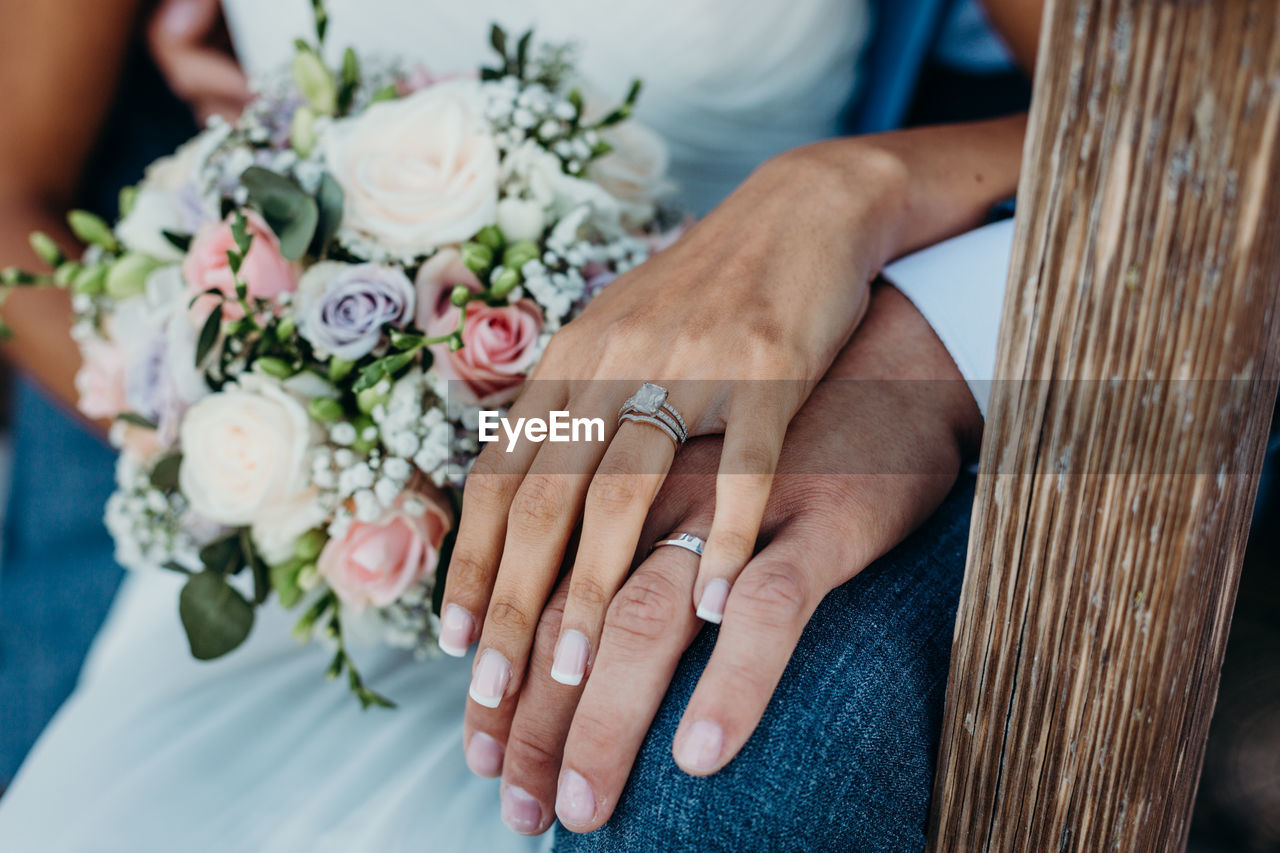 Midsection of newlywed couple holding hands in wedding ceremony