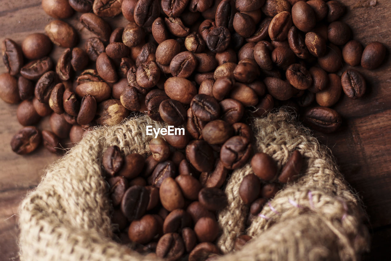 High Angle View Of Roasted Coffee Bean Spilled From Jute Bag