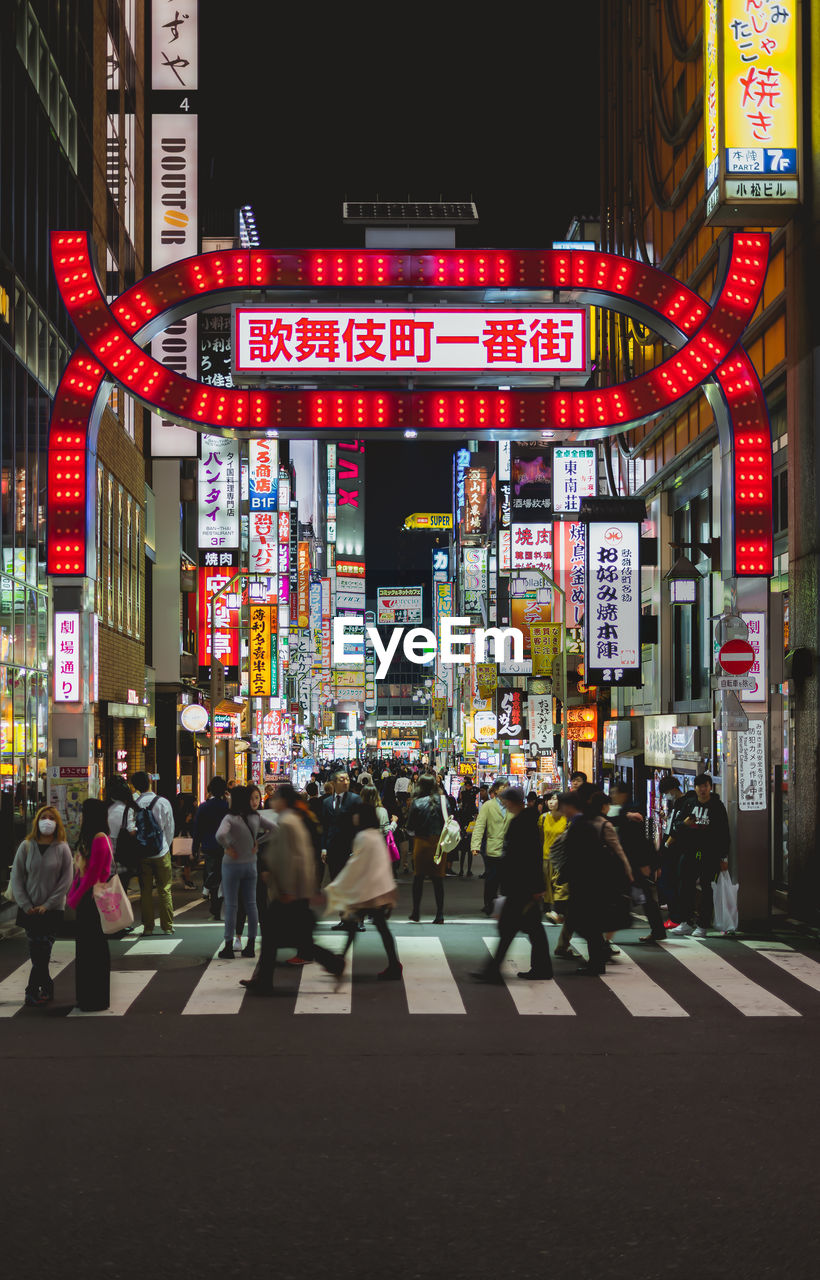 text, building exterior, architecture, communication, large group of people, night, city life, city, built structure, real people, illuminated, neon, store, women, outdoors, men, travel destinations, nightlife, crowd, people