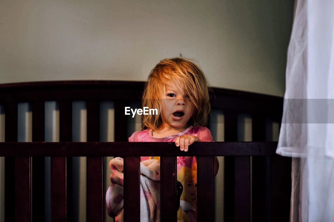 Portrait of girl standing in crib at home