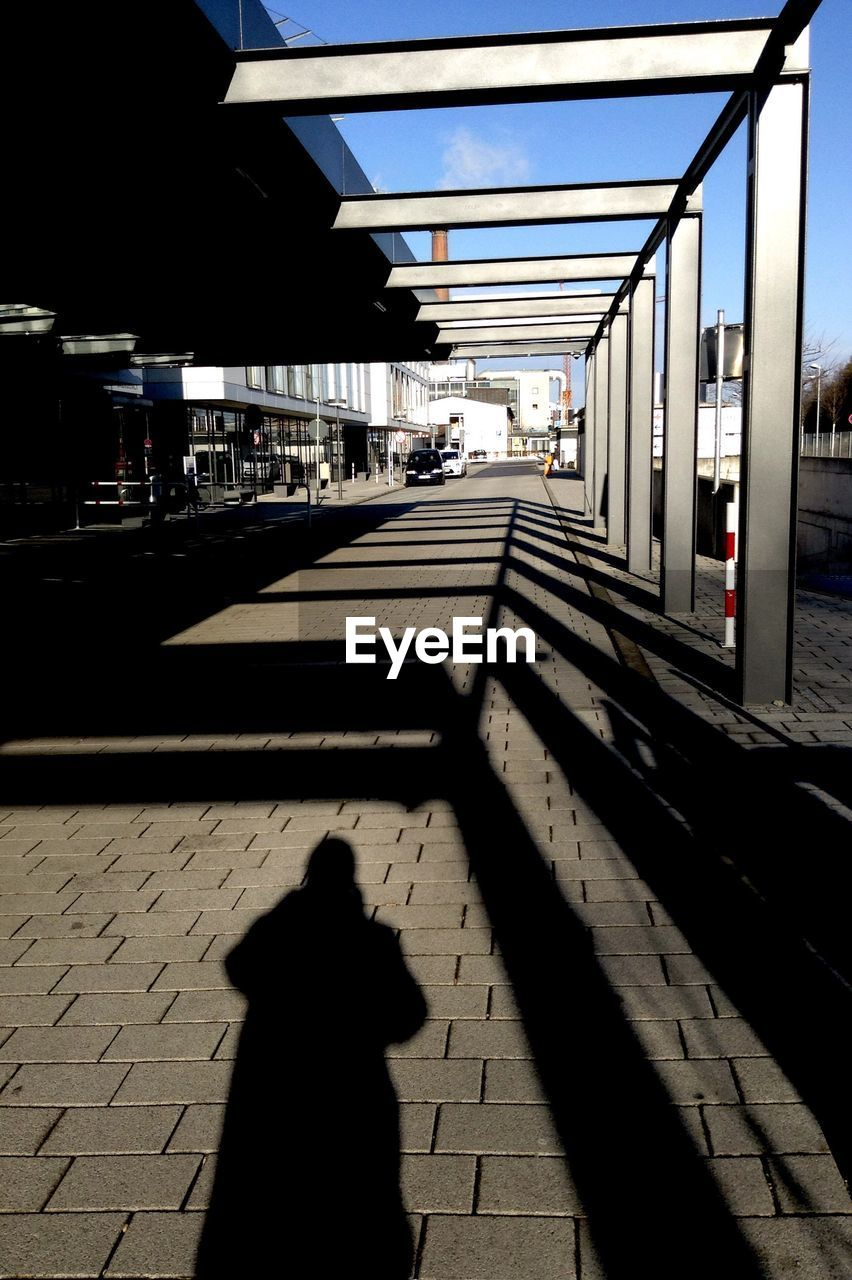 public transportation, real people, shadow, transportation, day, railroad station platform, one person, sunlight, outdoors, architecture, city, sky, people