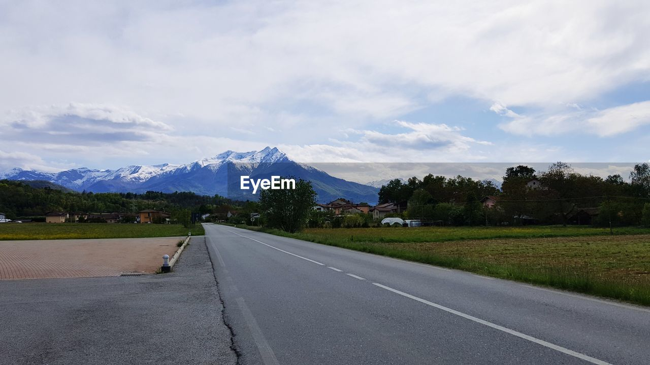 road, sky, transportation, mountain, cloud - sky, the way forward, direction, scenics - nature, beauty in nature, sign, mountain range, nature, plant, non-urban scene, tranquil scene, tranquility, no people, day, road marking, symbol, diminishing perspective, snowcapped mountain
