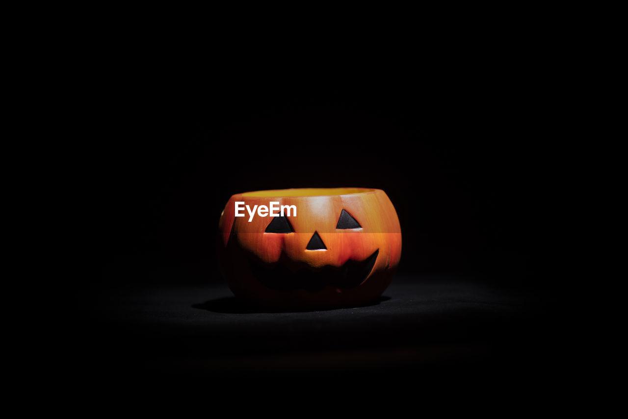 halloween, illuminated, pumpkin, jack o' lantern, face, anthropomorphic face, anthropomorphic, food, indoors, studio shot, copy space, no people, orange color, food and drink, close-up, black background, creativity, celebration, still life, dark