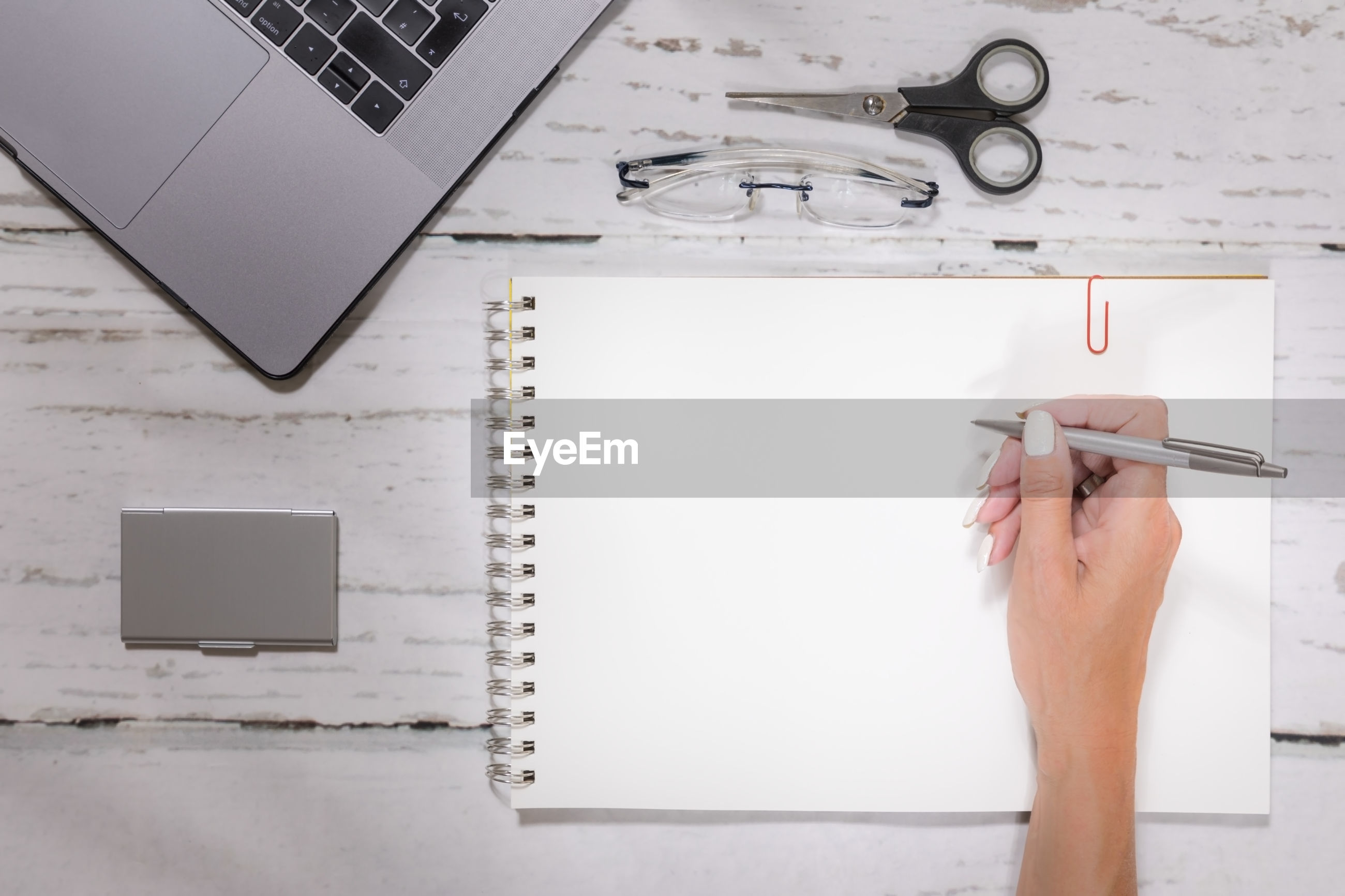 High angle view of woman hand writing on paper by laptop over table