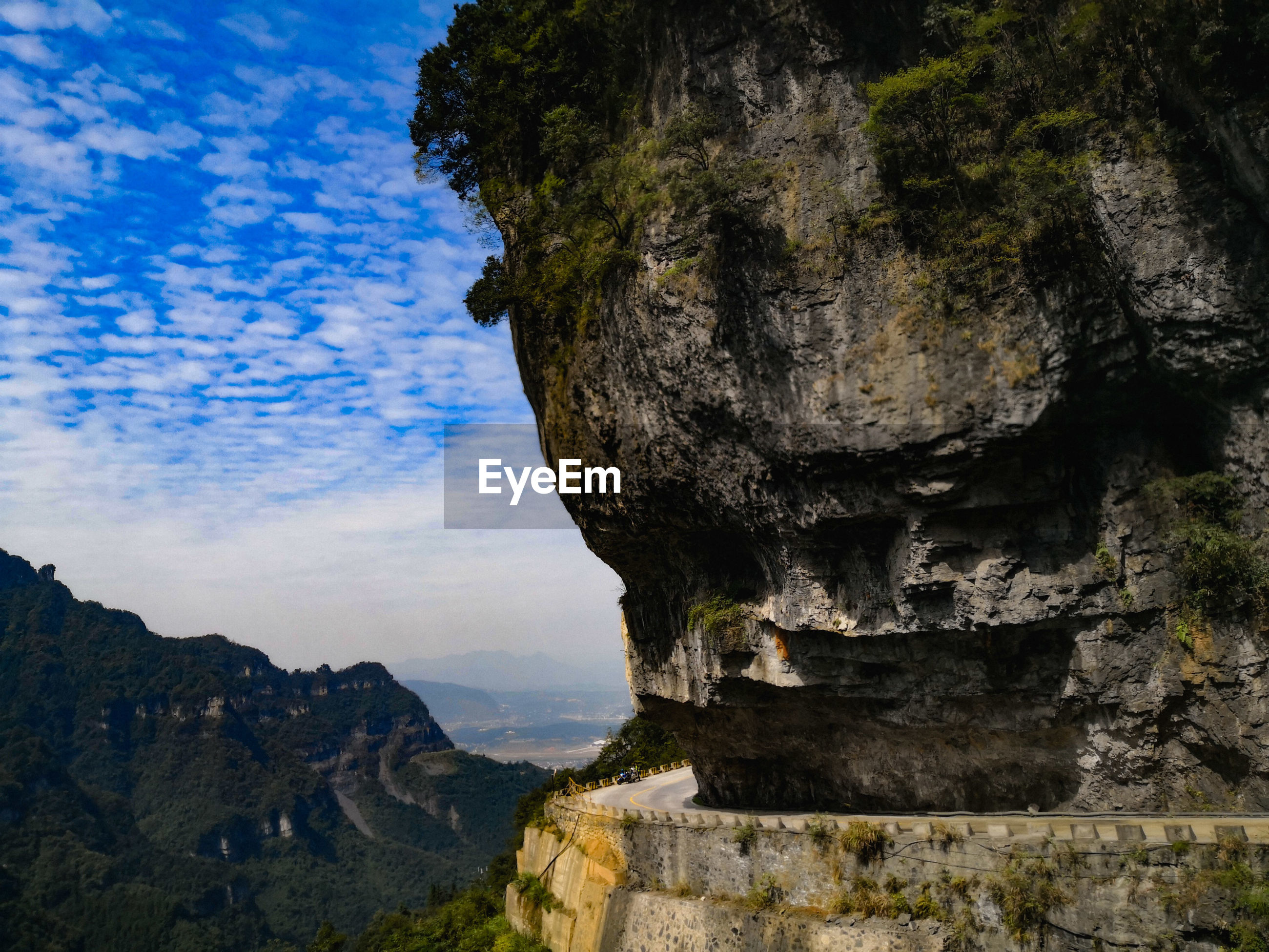ROCK FORMATION ON CLIFF AGAINST SKY