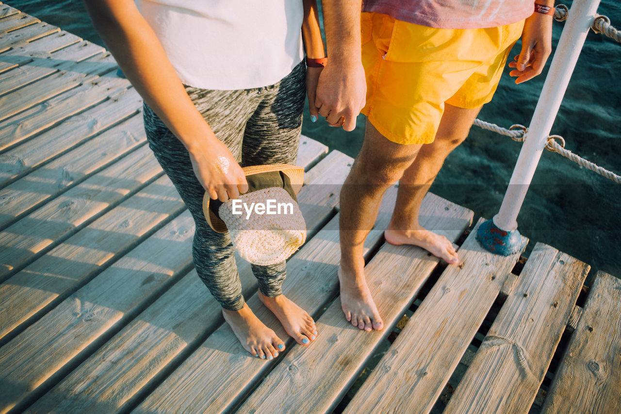 Low section of couple standing on boardwalk while holding hands