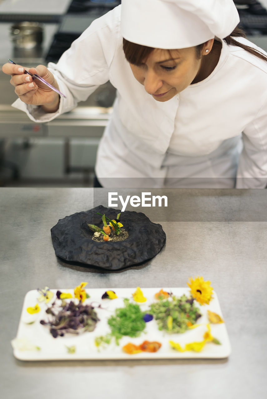 Woman garnishing food in commercial kitchen