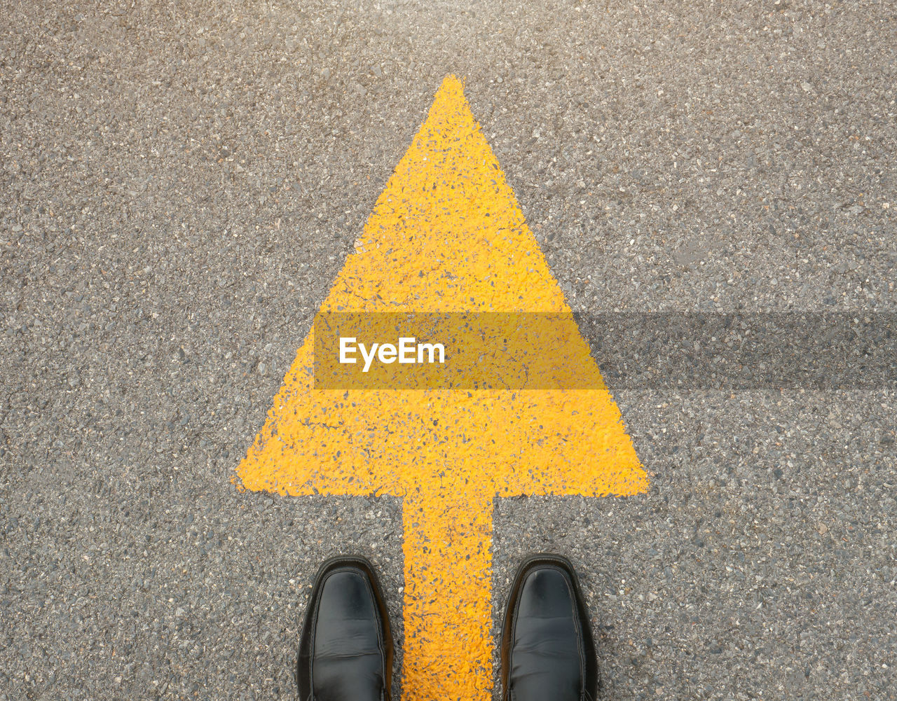 yellow, low section, shoe, standing, arrow symbol, sign, human body part, human leg, one person, body part, road, symbol, transportation, high angle view, direction, real people, guidance, day, personal perspective, outdoors, human foot, human limb
