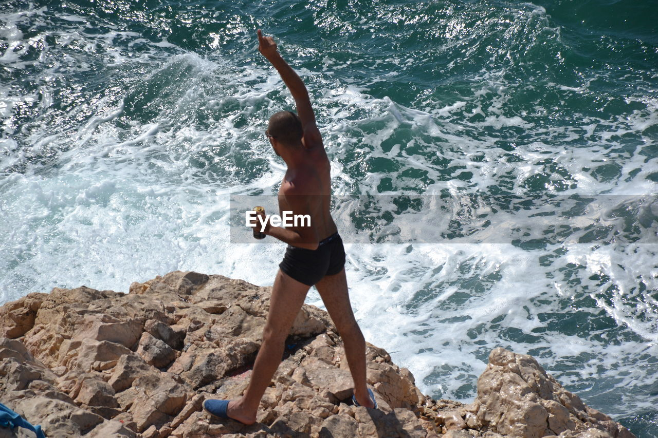 High Angle View Of Shirtless Man Pointing While Standing On Rocky Shore
