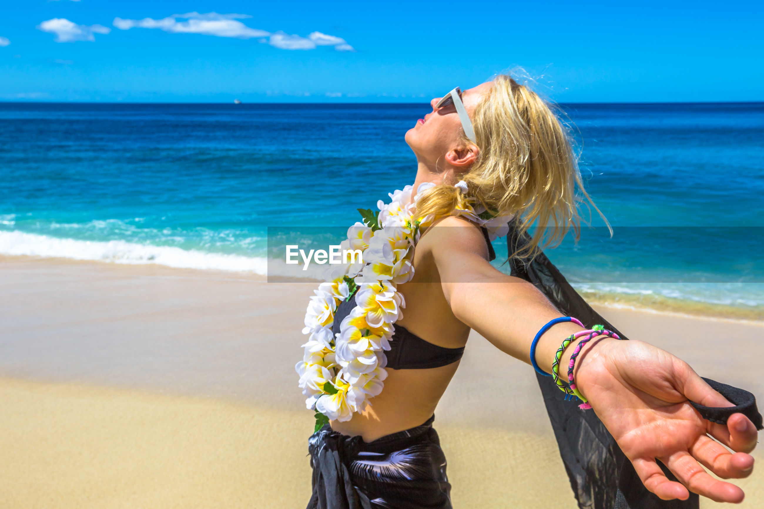 Side view of mature woman wearing floral garland while standing at beach