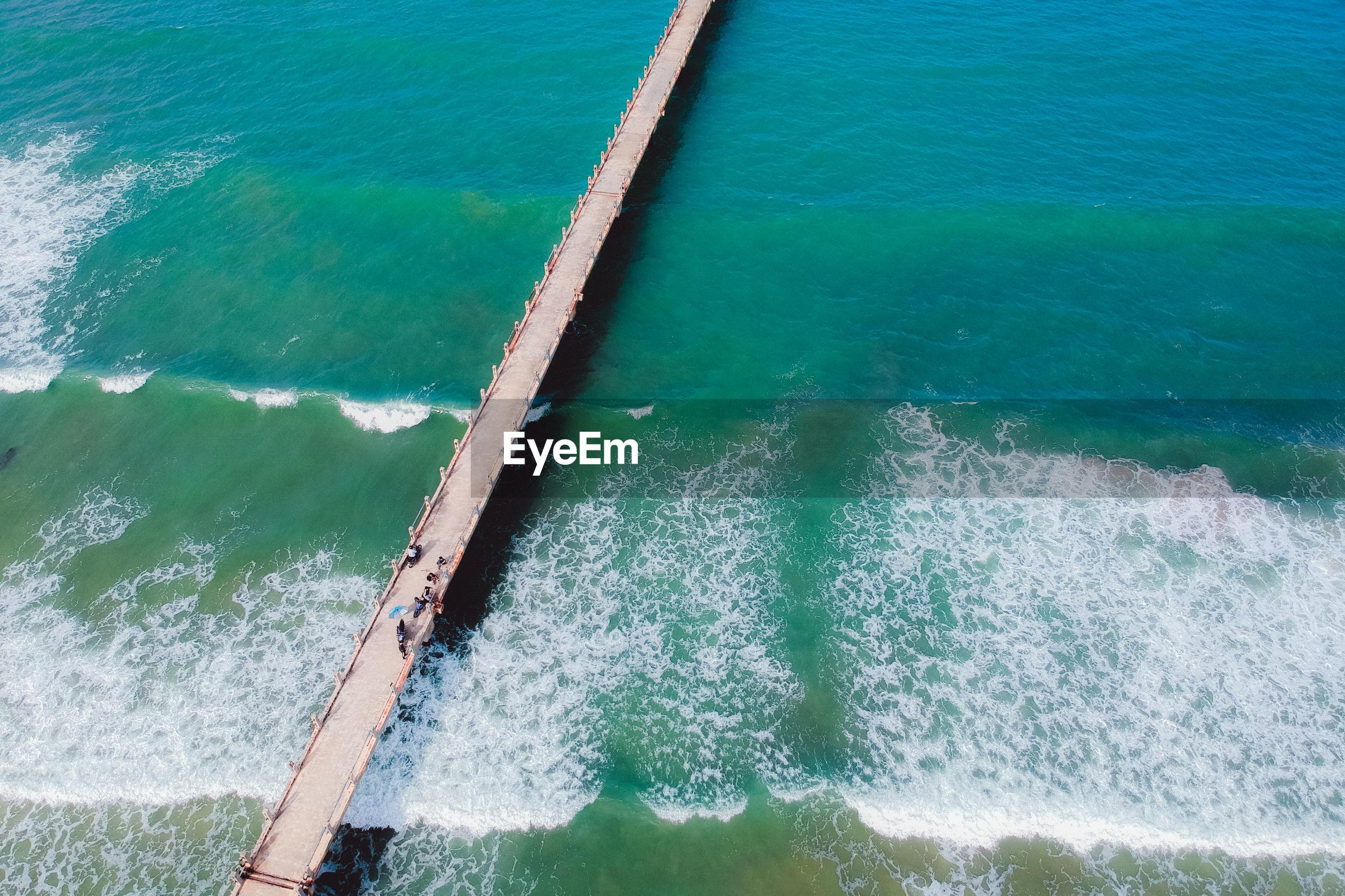 HIGH ANGLE VIEW OF WAVES SPLASHING ON SEA SHORE