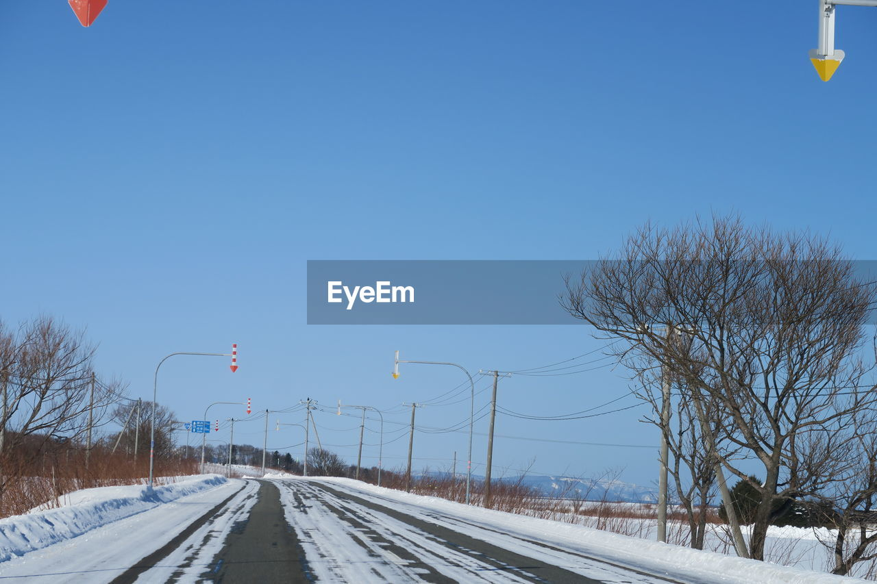 sky, cold temperature, winter, snow, transportation, tree, direction, nature, bare tree, the way forward, clear sky, no people, day, plant, blue, copy space, beauty in nature, road, white color, track, diminishing perspective, outdoors