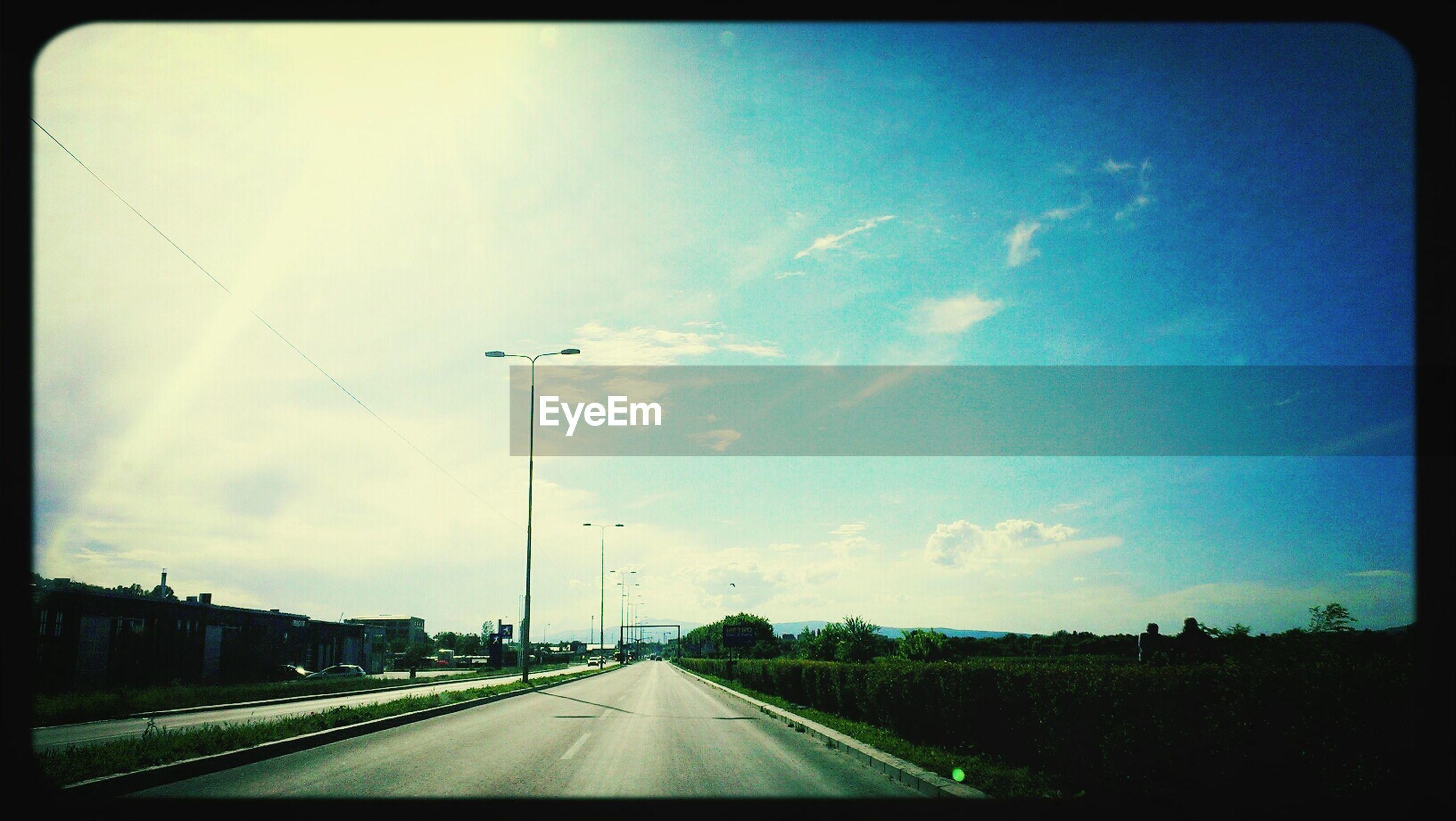 Empty street against blue sky