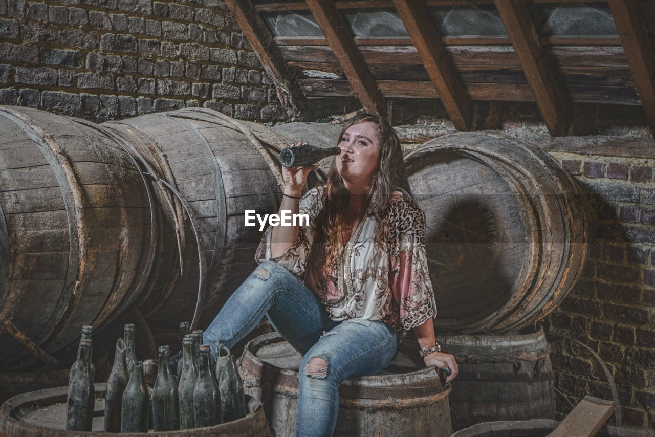 Portrait Of Smiling Woman Drinking Alcohol From Bottle While Sitting On Wooden Barrel At Abandoned Cellar