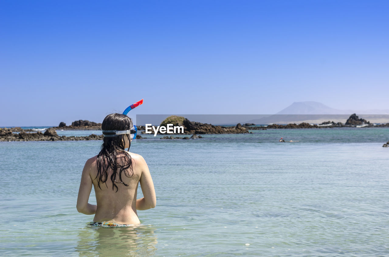 Rear View Of Shirtless Woman Snorkeling In Sea Against Clear Blue Sky