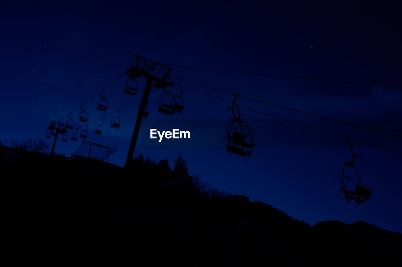 Low Angle View Of Silhouette Ski Lift Over Mountain Against Sky At Dusk