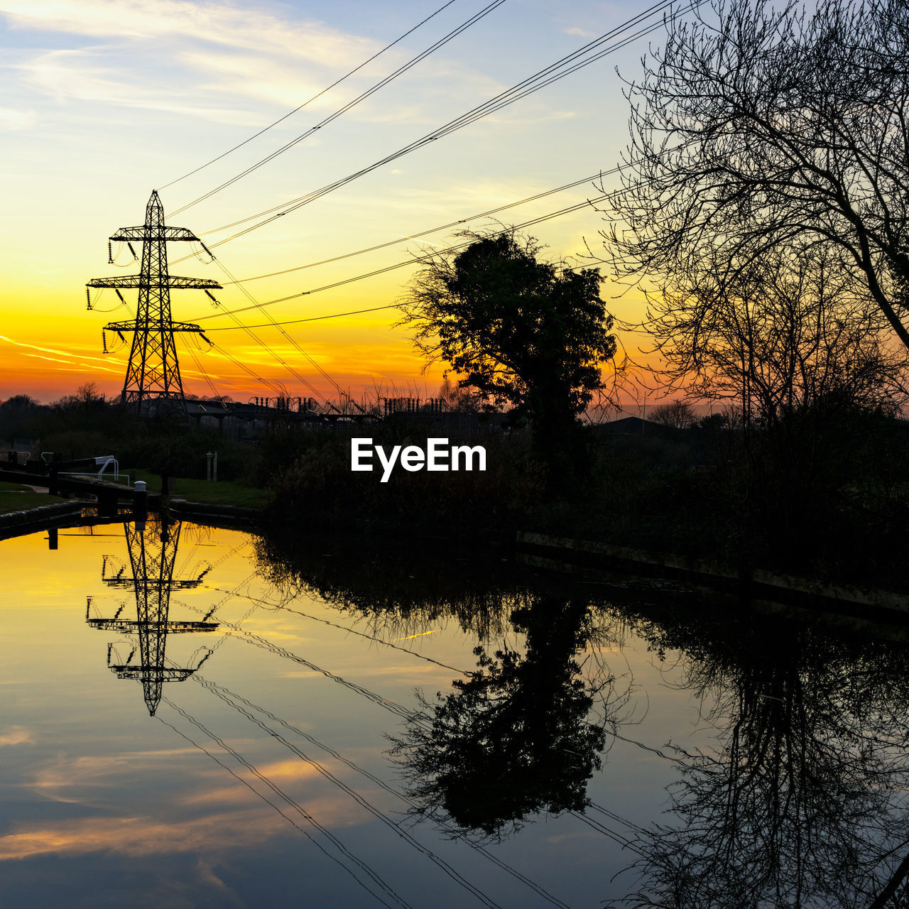 sunset, sky, reflection, tree, water, silhouette, electricity, plant, cable, power line, lake, electricity pylon, technology, scenics - nature, beauty in nature, orange color, tranquility, nature, tranquil scene, no people, power supply, outdoors