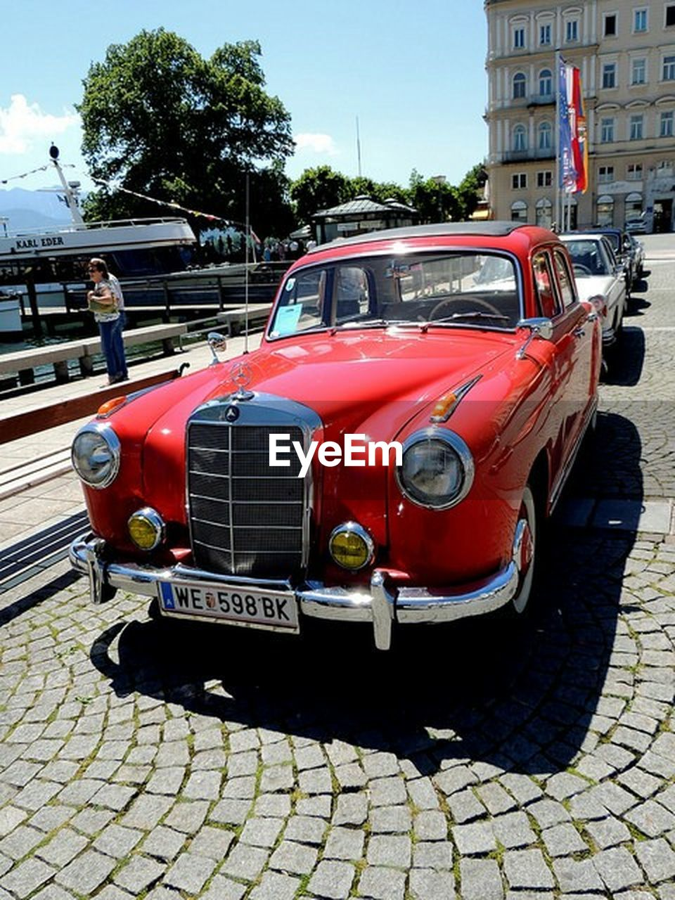 red, land vehicle, transportation, car, mode of transport, day, outdoors, old-fashioned, stationary, building exterior, architecture, built structure, no people, sky, city