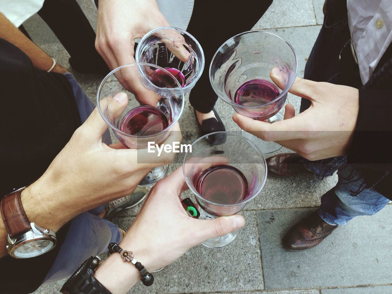 High Angle View Of People Holding Glasses With Drink On Street