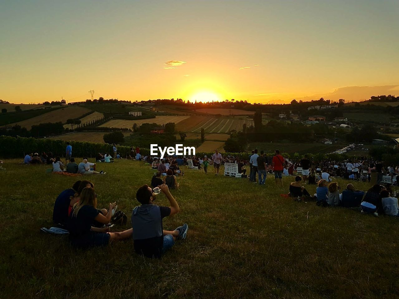 sunset, large group of people, grass, togetherness, real people, leisure activity, nature, relaxation, enjoyment, field, men, sitting, women, landscape, outdoors, lifestyles, beauty in nature, sky, people, adult, adults only, day