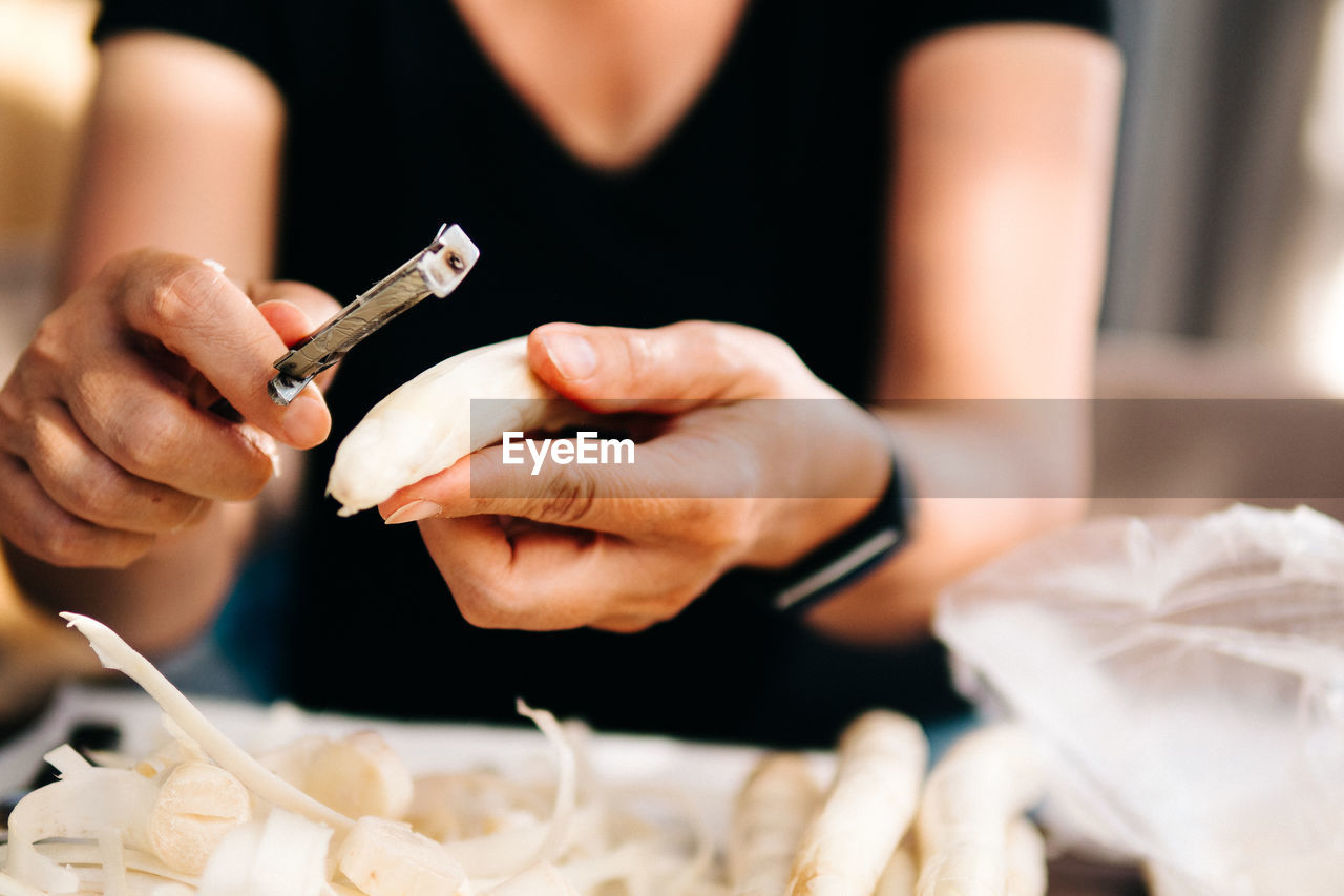 Midsection of woman peeling vegetable