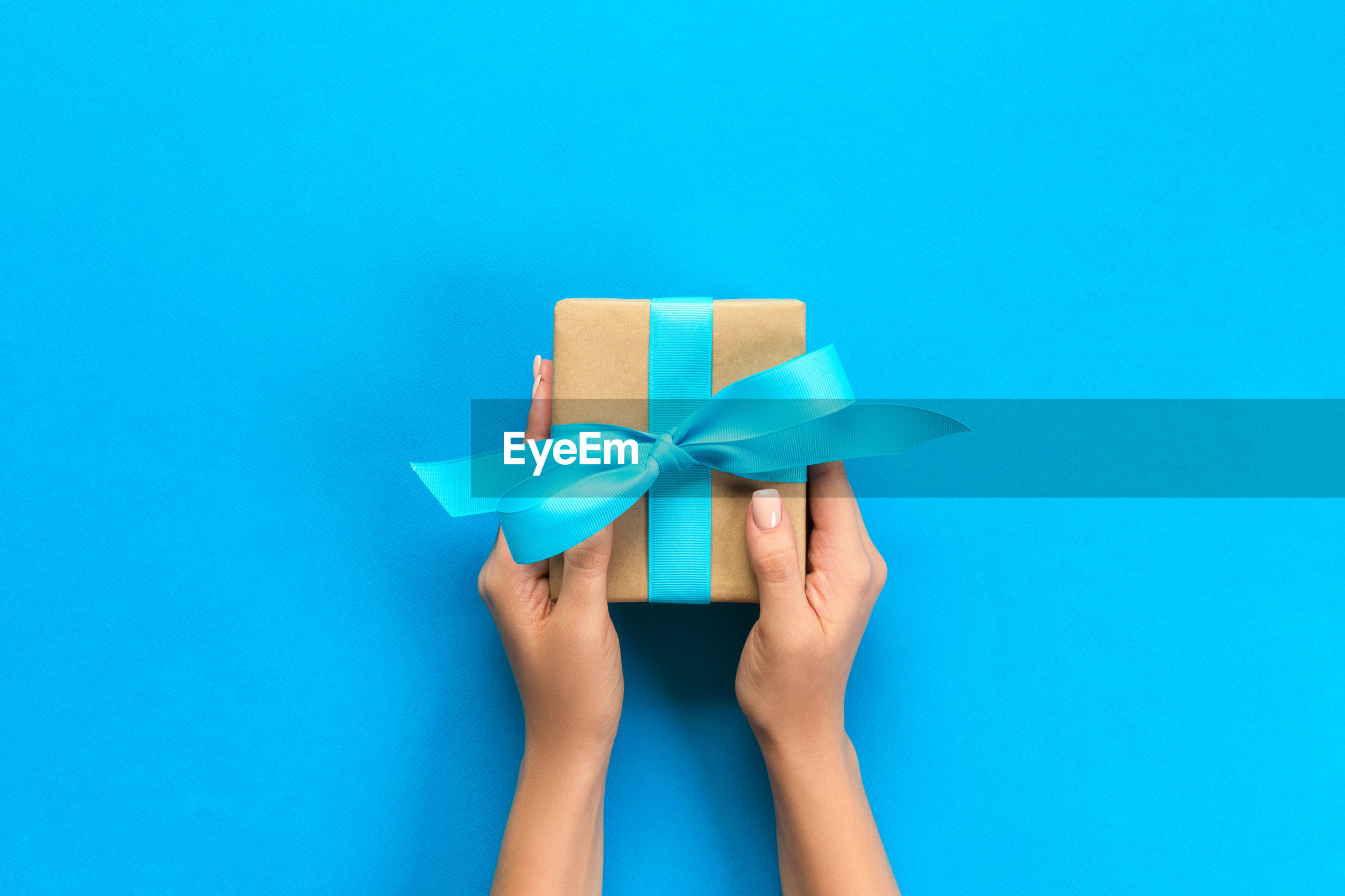 Cropped hands of woman holding gift box on blue background