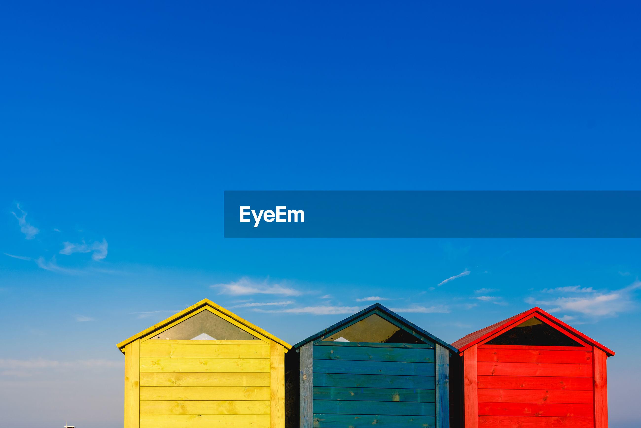 Multi colored beach huts against sky